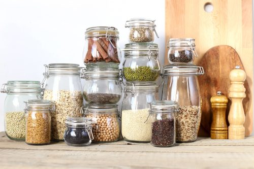Healthy foods in glass jars. Cereals, seeds, legumes, spices. On a wooden table.