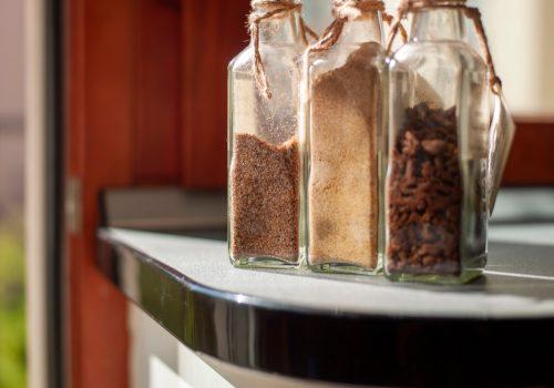 Koleksi botol dengan rempah-rempah di atas meja, di dalam ruangan di siang hari