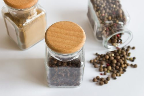 Closeup mockup template with three jars glass hermetic bottles with wooden caps and spices seasonings on white background.