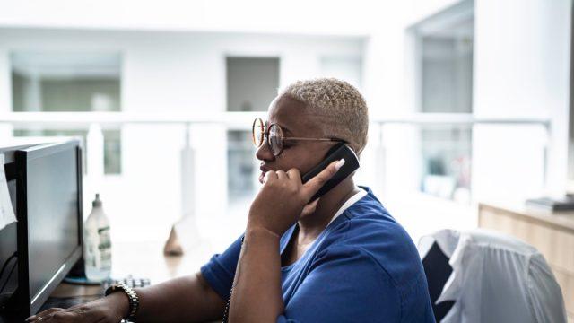 Secretary talking on telephone at hospital reception