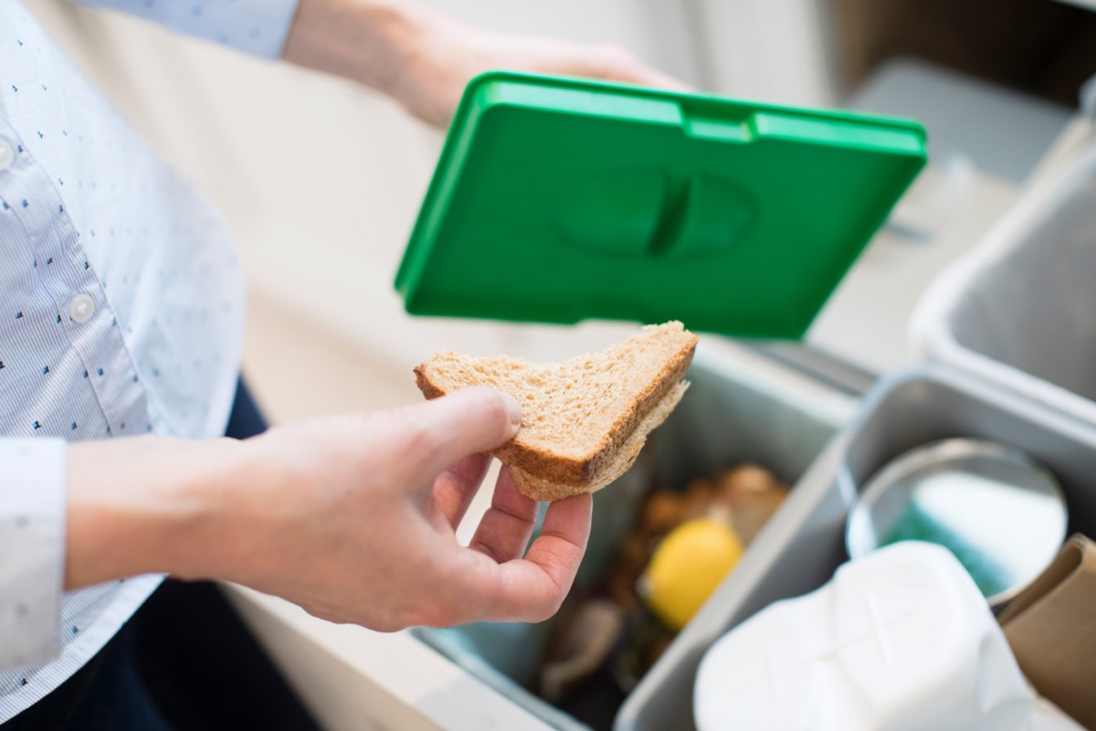 person throwing away sandwich