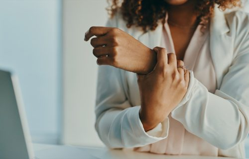 Shot of an unrecognisable businesswoman experiencing wrist pain while working in a modern office
