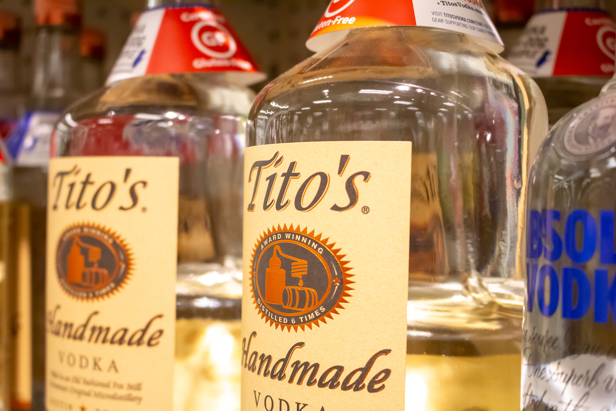 Two glass bottles of Tito's Handmade Vodka on a shelf at a grocery store