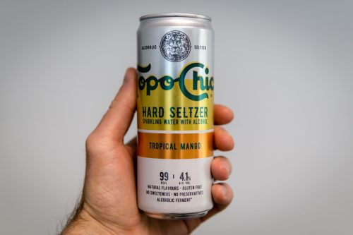Munich, Germany, August 03rd 2021 : Ice cold Can of Topo Chico Tropical Mango holding in hand