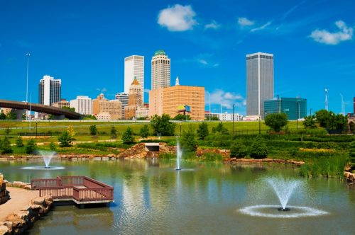 Tulsa skyline with a park, pond, and fountains in the foreground.