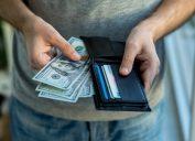 Man placing USA Dollar bills into wallet