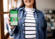Defocussed young woman holding smartphone with certificate of vaccination against the Covid-19