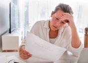 Woman looking worried holding paperwork at home. She is reading a financial bill or a letter with bad news. She looks very stressed and upset. There is a laptop computer on the table