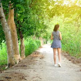 young woman walking under tree arbor outdoors
