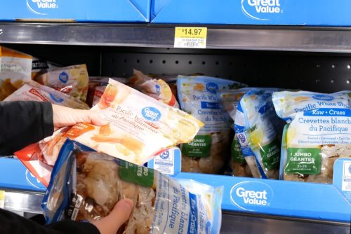Coquitlam, BC, Canada - April 30, 2019 : Motion of woman buying great value white shrimp inside Walmart store