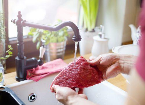 Seorang pria mencuci daging di wastafel