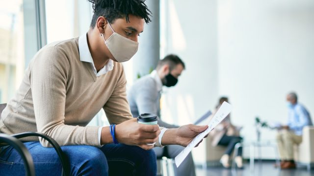 man with a face mask waiting in a room