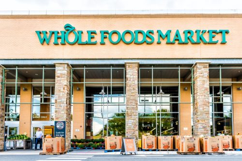 Fairfax, USA - September 8, 2017: Green Whole Foods Market grocery store sign on exterior building in city in Virginia with autumn displays of pumpkins for Halloween