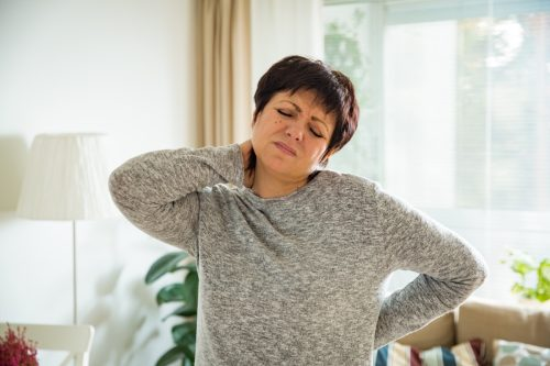 Mature woman suffering from backache at home. Massaging neck with hand, feeling exhausted, standing in living room.