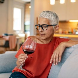 Lonely mature woman holding glass of alcoholic drink while sitting on sofa at home during the day.