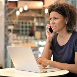 A young woman sitting in a cafe while answering a phone call with a confused look on her face