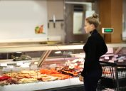 young woman in turtleneck buying fish