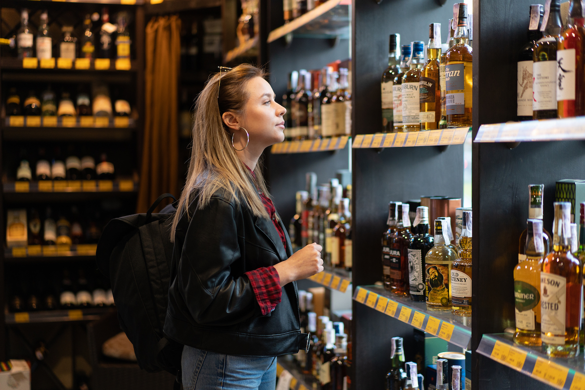 Woman in a liquor store looking at a shelf with bottles of whiskey.