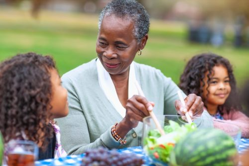 Grandmother with two granddaughters at picnic in park