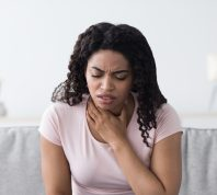 A young woman sitting on the couch and holding her throat while suffering from COVID symptoms