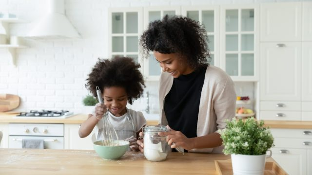 A mother helping her daughter mix together ingredients for baking a cake or muffins