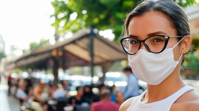 A young woman standing outside while wearing a face mask