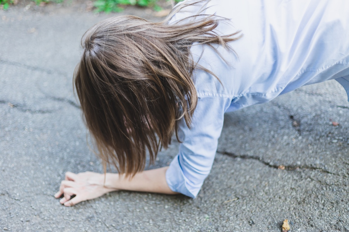 woman in blue shirt falling on ground
