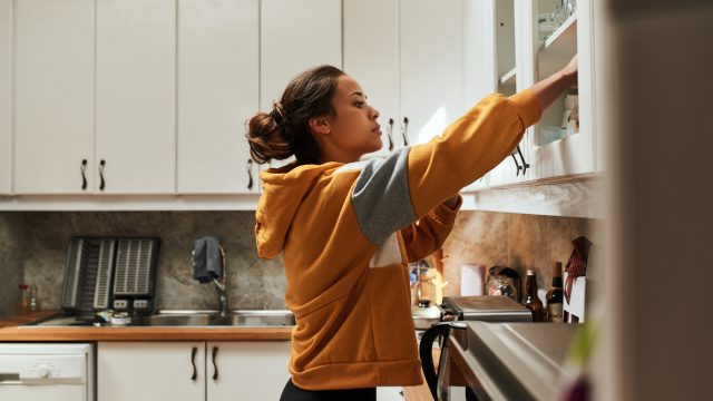 A young woman reaching inside a kitchen cabinet