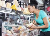 young woman looking inside deli case at supermarket