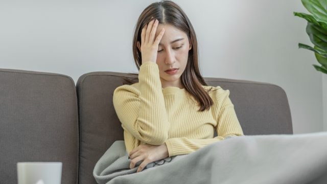 A young woman sitting on the couch holding her head while sick with COVID symptoms