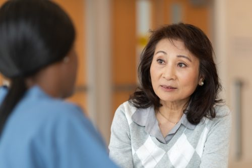 nurse is teaching her adult patient how to correctly use an asthma inhaler.