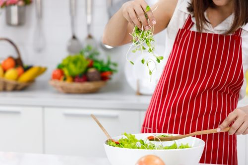 Woman chef in red apron putting sunflower sprout in salad bowl.