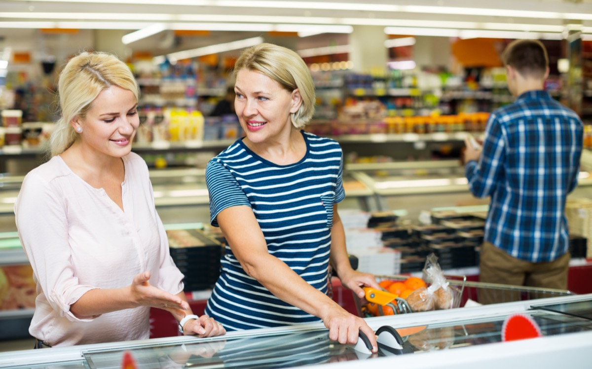 two middle-aged women shopping at supermarket