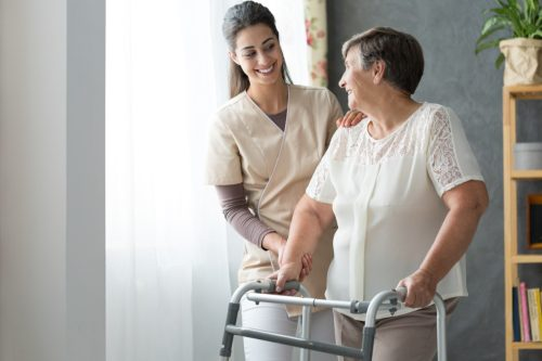 Worker helping a woman in a nursing home