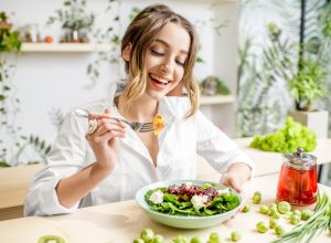 A young woman eating a salad at a kitchen table