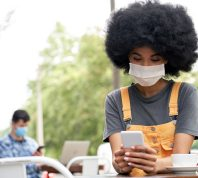 A young woman sitting outdoors at a cafe while checking her phone and wearing a mask
