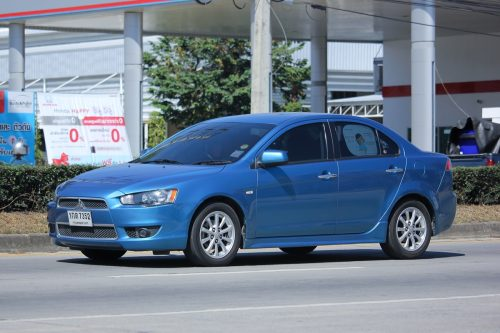 a blue Mitsubishi Lancer car driving on the road