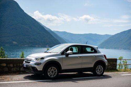 a white Fiat 500X car next to a mountain
