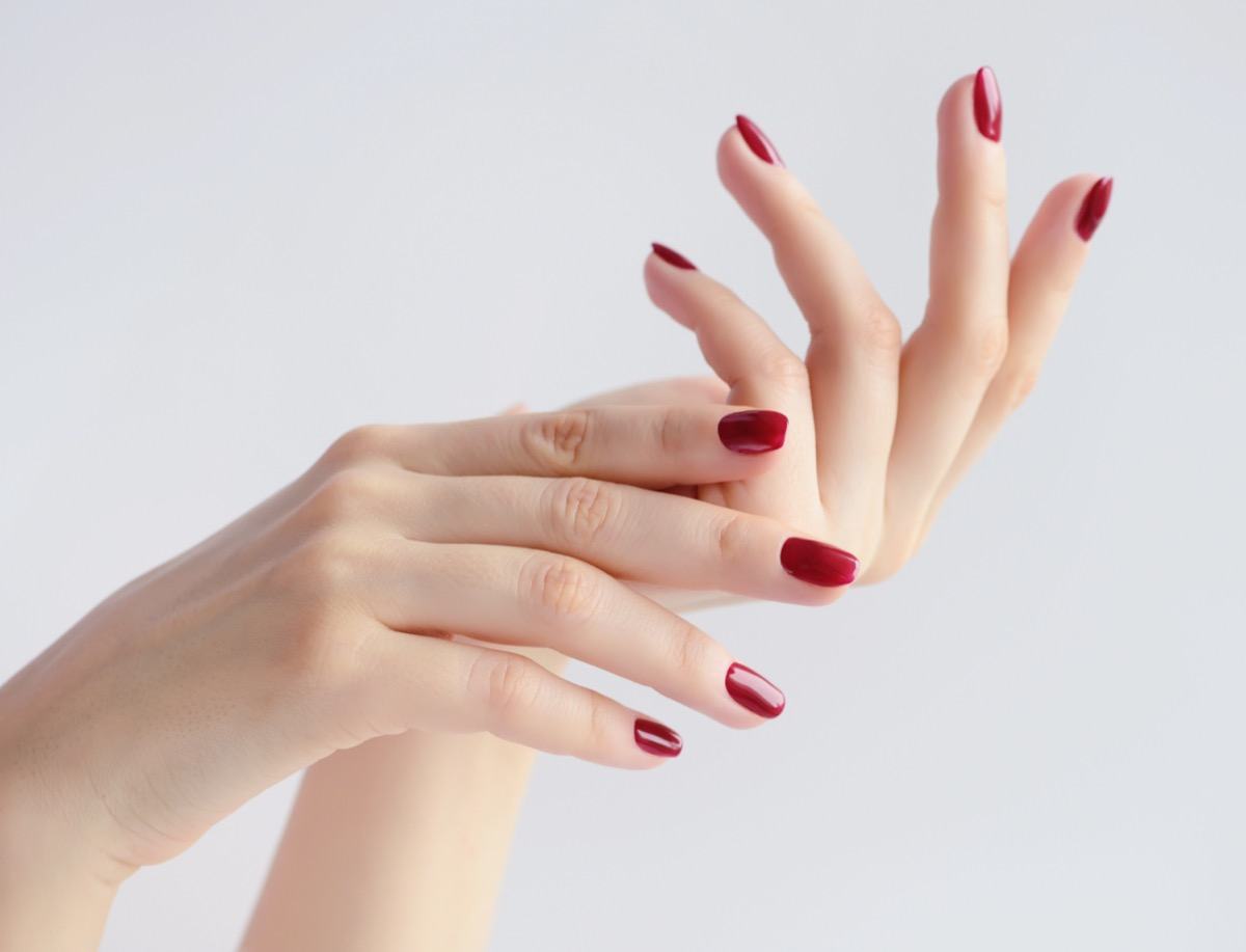 Closeup on woman's hands with red manicure