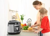 Woman and daughter cooking vegetables in Instant Pot or multi-cooker