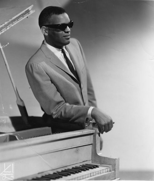 Ray Charles leaning on his piano in 1956