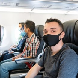 Airplane passengers are wearing medical masks on their faces. Air travel during the coronavirus pandemic. Airlines requirements