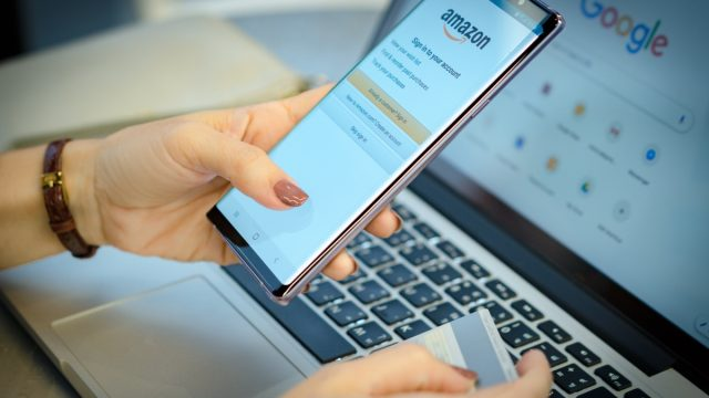 person holding smartphone to access amazon account
