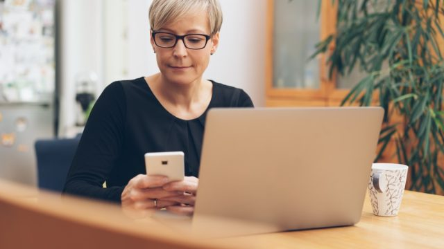 Frowning businesswoman reading a message on her mobile phone as she sits working at a laptop
