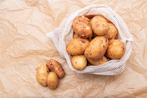 Raw fresh organic potatoes. Full bag of potatoes. Burlap sack with potatoes. Space for text,