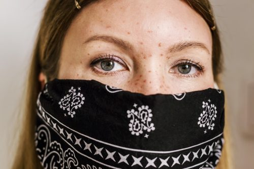 Head portrait of young woman dressed facial protected bandana black mask.