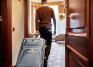 Cropped shot of middle-aged businessman in casual wear with suitcase entering his room in the background. A door with a sign at the front. Horizontal shot. Selective focus