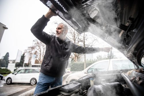 Steam Coming Out of Car Engine While Mature Man is Opening the Hood .
