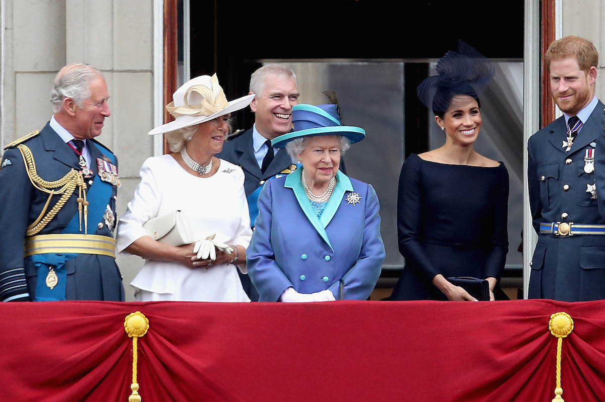 Prince Charles, Prince of Wales, Prince Andrew, Duke of York, Camilla, Duchess of Cornwall, Queen Elizabeth II, Meghan, Duchess of Sussex, and Prince Harry, Duke of Sussex, watch the RAF flypast on the balcony of Buckingham Palace, as members of the Royal Family attend events to mark the centenary of the RAF on July 10, 2018 in London, England