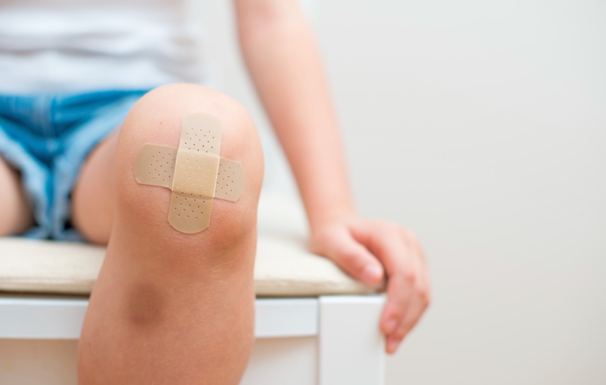 child with two bandages on their bruised knee
